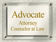 clear door sign affixed to a beige wall with gold lettering which reads advocate attorney counselor at law