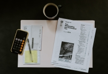 checkbook duplicate, post-it note, and white printer papers showing text about taxes in a beige folder on a black surface with a cup of coffee and iPhone in a yellow case with calculator feature