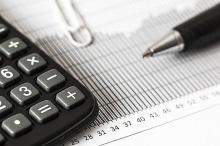 black calculator white paper clip and black pen on white paper chart