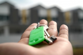 green keychain and keys in left hand with townhouses in backgound