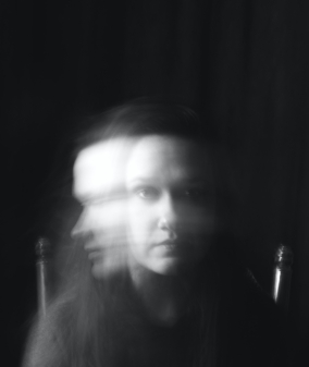 black and white photo of a woman with distortion of the image to show motion