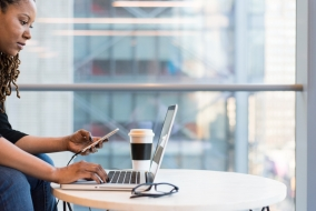 black female using a laptop and phone on a table with glasses and coffee placed nearby