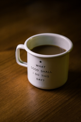 white and black ceramic cup with 'what good shall I do to this day' on it - filled with brown liquid on brown wooden surface