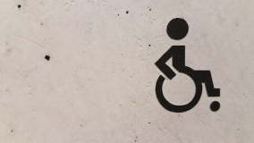concrete wall with affixed black 'wheelchair' symbol decal