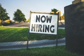 white and black now hiring sign with parking lot and grass in background