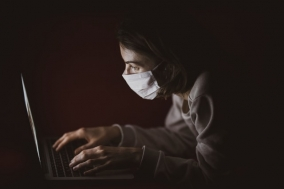 woman in white shirt wearing a mask using laptop computer