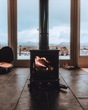wood burning stove in room with windows and winter scene in background